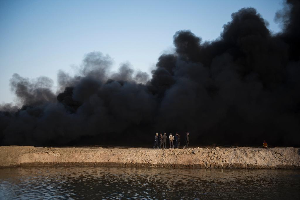 Oil wells have belched columns of toxic black smoke for three months, caking everything in and around Qayyarah in a thick layer of soot (AFP Photo/Odd Andersen)