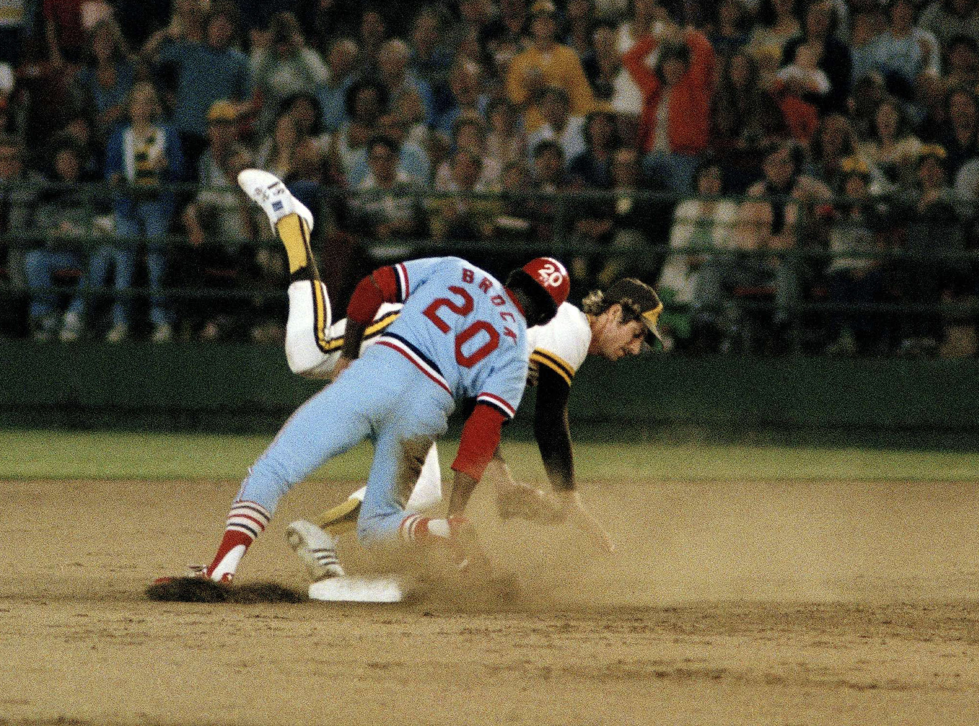 FILE - In this Aug. 30, 1977, file photo, St. Louis Cardinals' Lou Brock (20) lands on his feet after stealing second base in the seventh inning against the San Diego Padres, breaking Ty Cobb's major league record of 892 stolen bases, in San Diego, Calif. Padres shortstop Bill Almon falls after missing the throw. Hall of Famer Brock, one of baseball's signature leadoff hitters and base stealers who helped the Cardinals win three pennants and two World Series titles in the 1960s, has died. He was 81. (AP Photo, File)