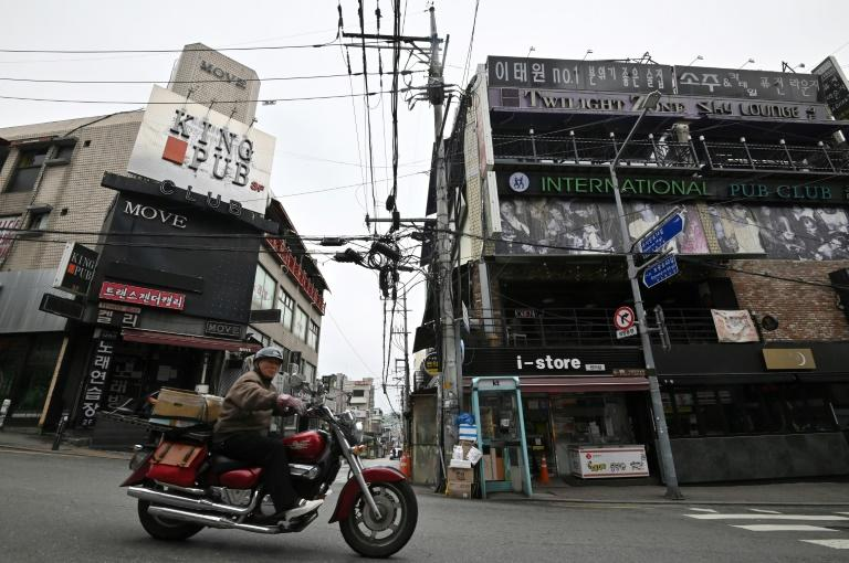A man rides a motorcycle along a street in the popular nightlife district of Itaewon in Seoul (AFP Photo/Jung Yeon-je)