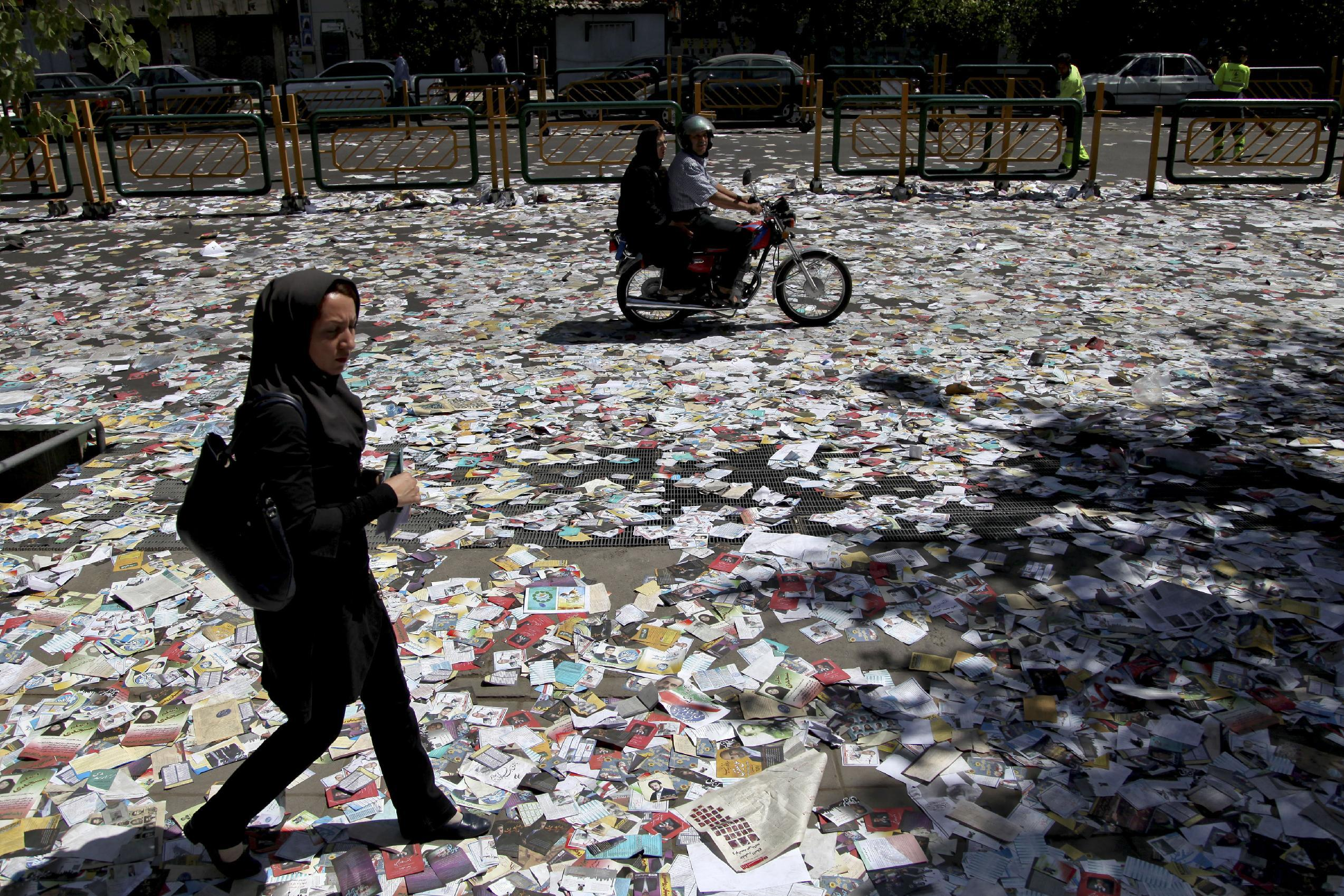 People make their way walking over electoral leaflets, covering the street after Friday prayers in Tehran, Iran, Friday, June 7, 2013. Iranian Presidential election will be held on June 14, 2013. (AP Photo/Ebrahim Noroozi)