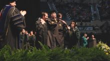 MBA student who uses wheelchair walks across stage at commencement ceremony