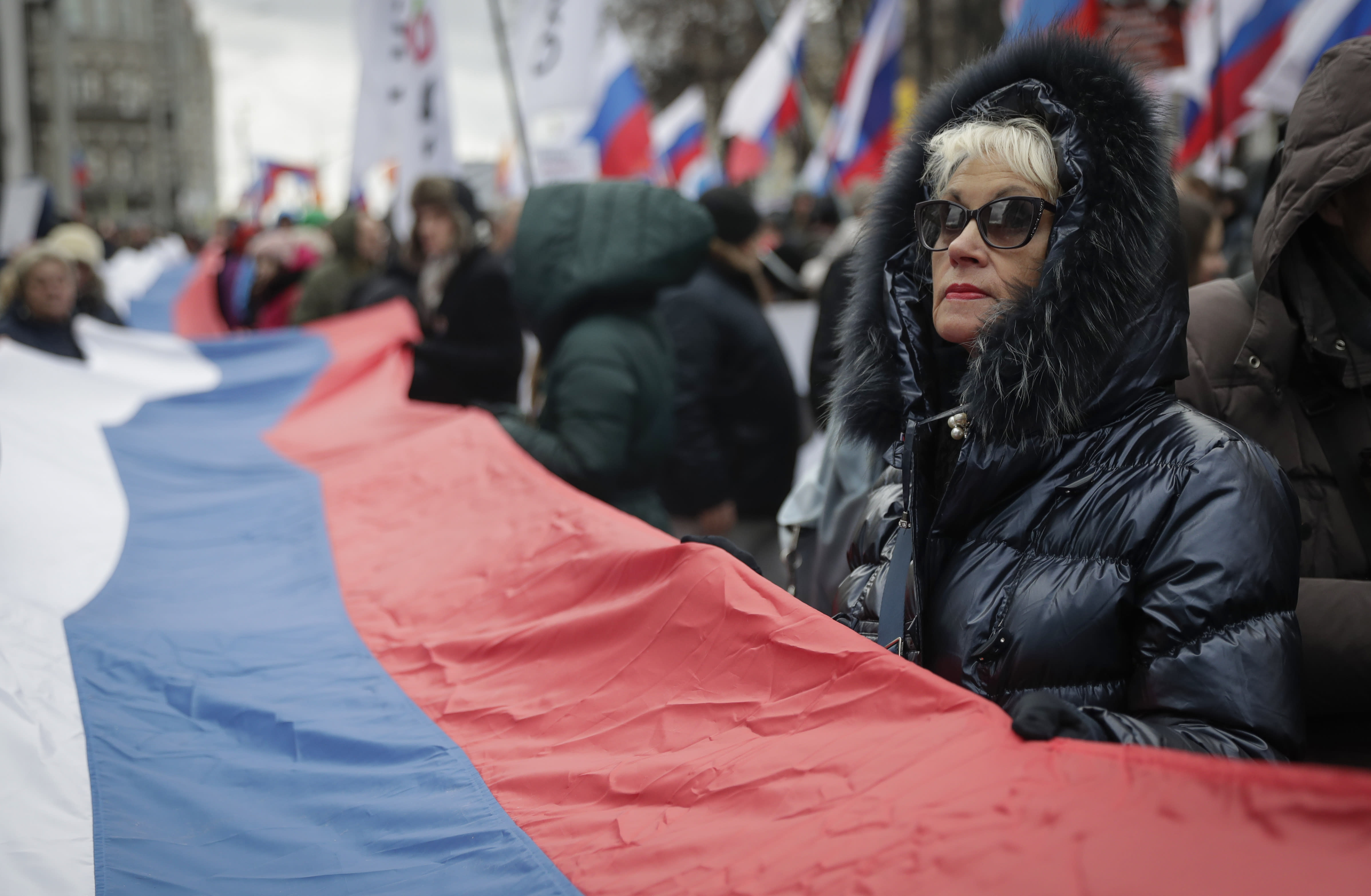 Demonstrators carry a Russian state flag as they gather to commemorate the anniversary of the death of opposition leader Boris Nemtsov in Moscow, Russia, Saturday, Feb. 29, 2020. Nemtsov, a charismatic Russian opposition leader and sharp critic of President Vladimir Putin, was gunned down on Feb. 27, 2015 near the Kremlin in Moscow, Russia. (AP Photo/Pavel Golovkin)