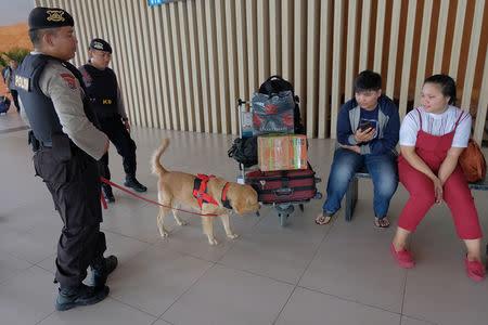Indonesian policemen K-9 unit patrols with dog at arrivals terminal at I Gusti Ngurah Rai International Airport ahead of Christmas and New Year holiday in Bali