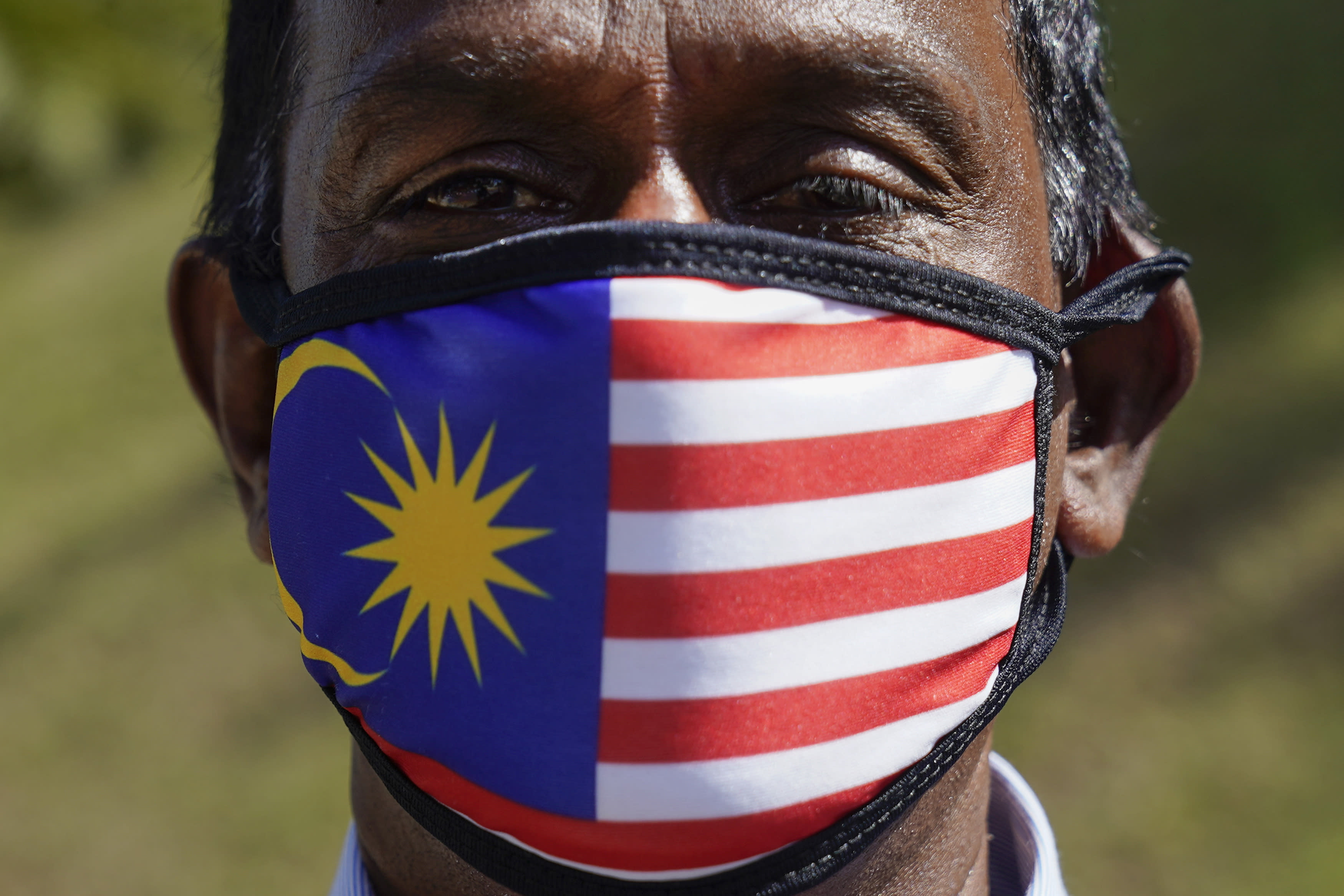 A supporter of People's Justice Party wearing a national flag face mask as he gathers with others outside the National Palace in Kuala Lumpur, Malaysia, Wednesday, Feb. 26, 2020. Malaysia's ruling alliance collapsed this week after 94-year-old Prime Minister Mahathir Mohamad resigned and dozens of lawmakers defected in an audacious attempt to form a new government. The political earthquake occurred less than two years after the alliance won a historic election that ousted a corruption-tainted coalition that had ruled for 61 years. (AP Photo/Vincent Thian)