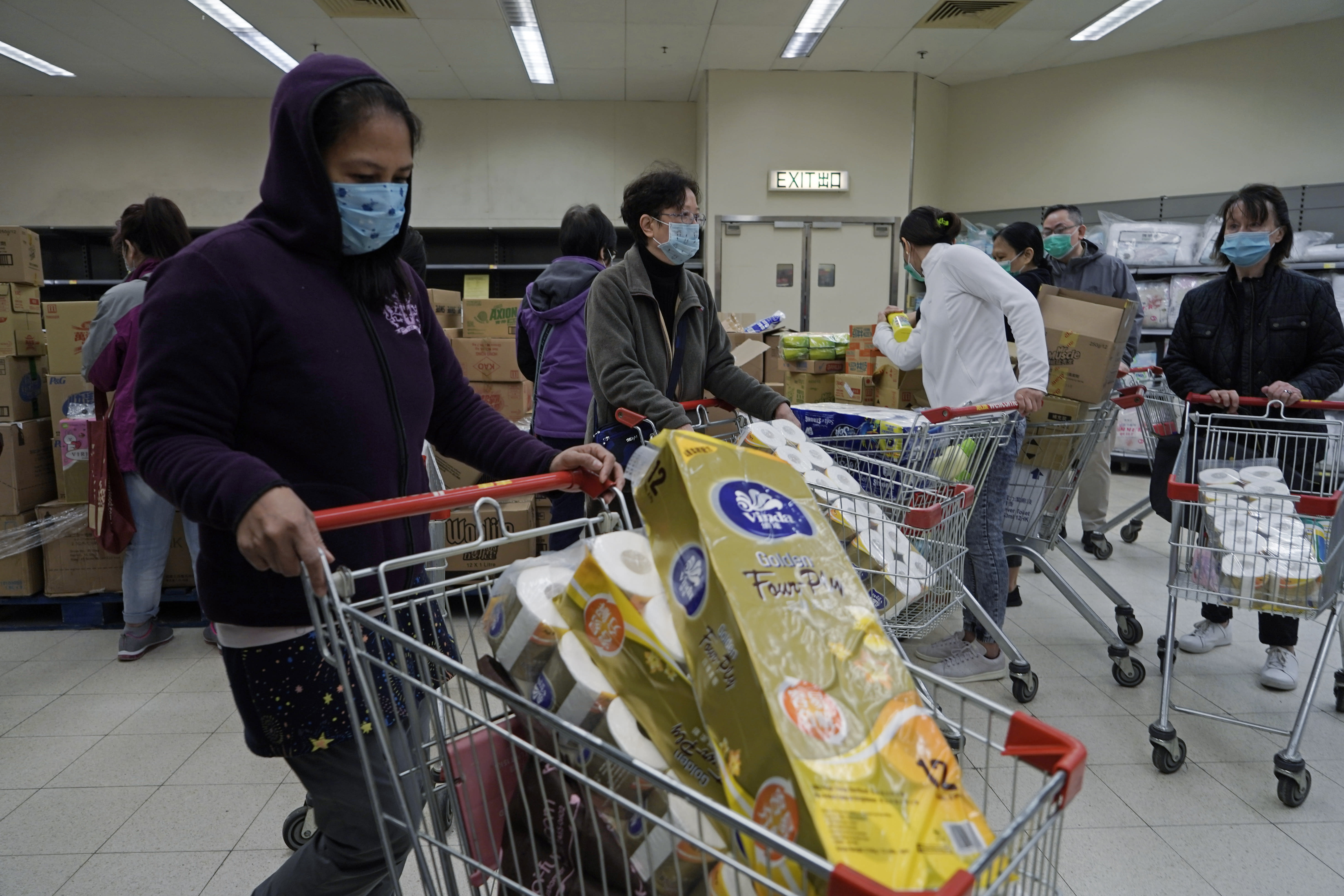 Customers wearing masks, purchase tissue papers in a supermarket in Hong Kong, Saturday, Feb. 8, 2020. Widespread panic-buying of essentials such as toilet rolls and rice has hit in Hong Kong, a knock-on effect of the virus outbreak in mainland China. (AP Photo/Kin Cheung)