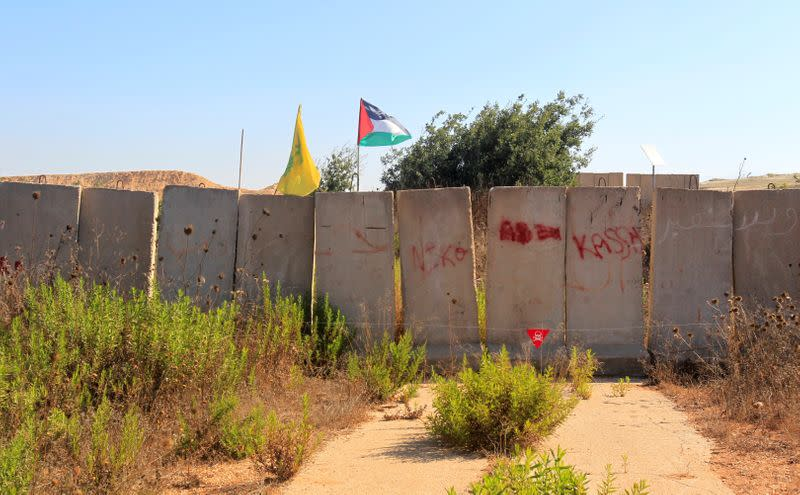 Palestinian and Hezbollah flags are seen in Houla village near the Lebanese-Israeli border