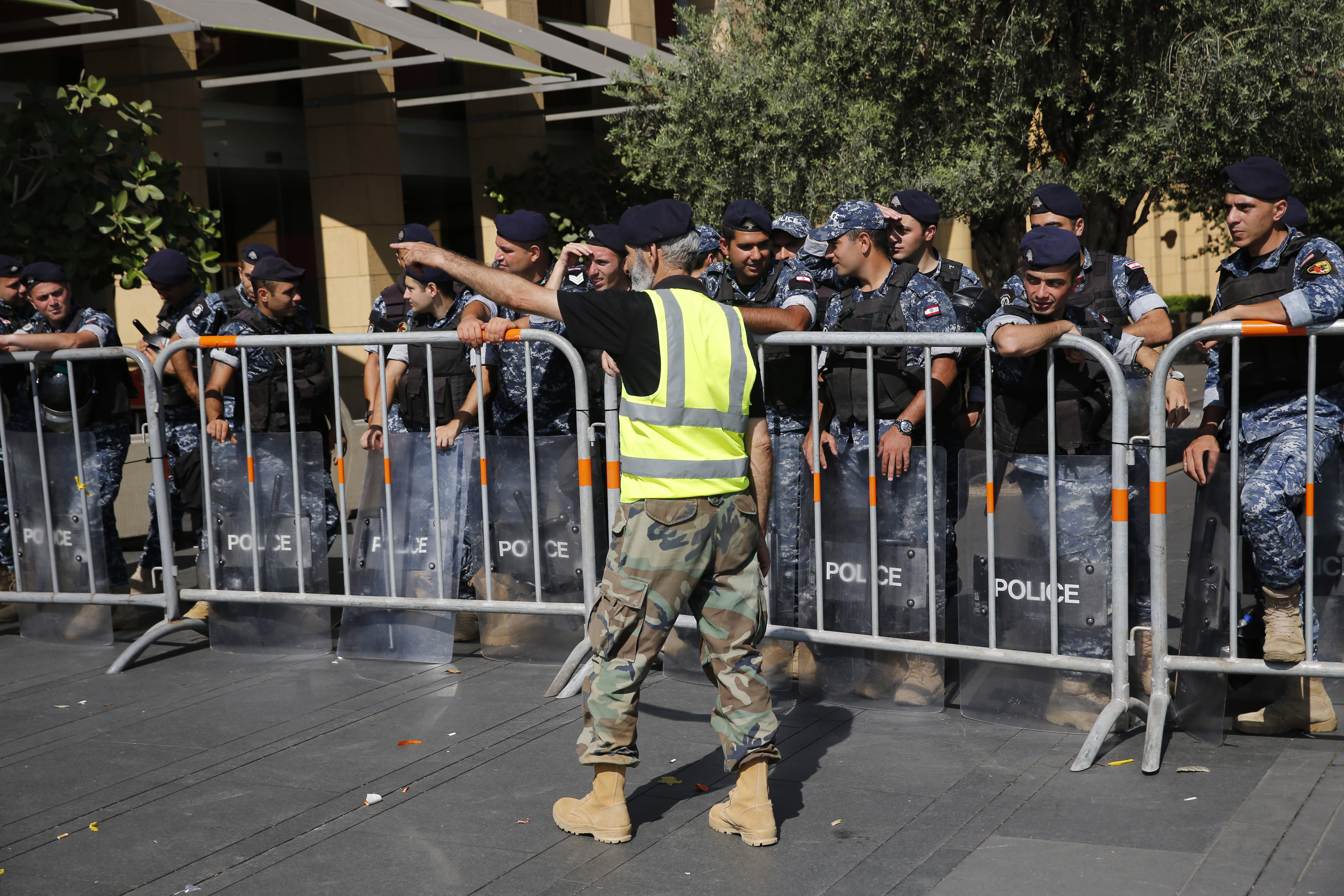 A retired Lebanese retired soldier, in yellow vest, protests in front of riot police who blocked a road leading to the parliament building where lawmakers and ministers are discussing the draft 2019 state budget, in Beirut, Lebanon, Tuesday, July 16, 2019. The lawmakers have begun discussing the budget amid tight security and limited protests against proposed austerity measures. The proposed budget aims to avert a financial crisis by raising taxes and cutting public spending in an effort to reduce a ballooning deficit. (AP Photo/Hussein Malla)