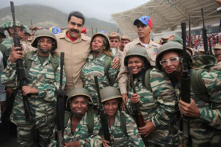 Venezuela's President Nicolas Maduro (back row 2nd L) poses for a photo with militia members during a military parade in La Guaira, Venezuela May 21, 2016. Miraflores Palace/Handout via REUTERS