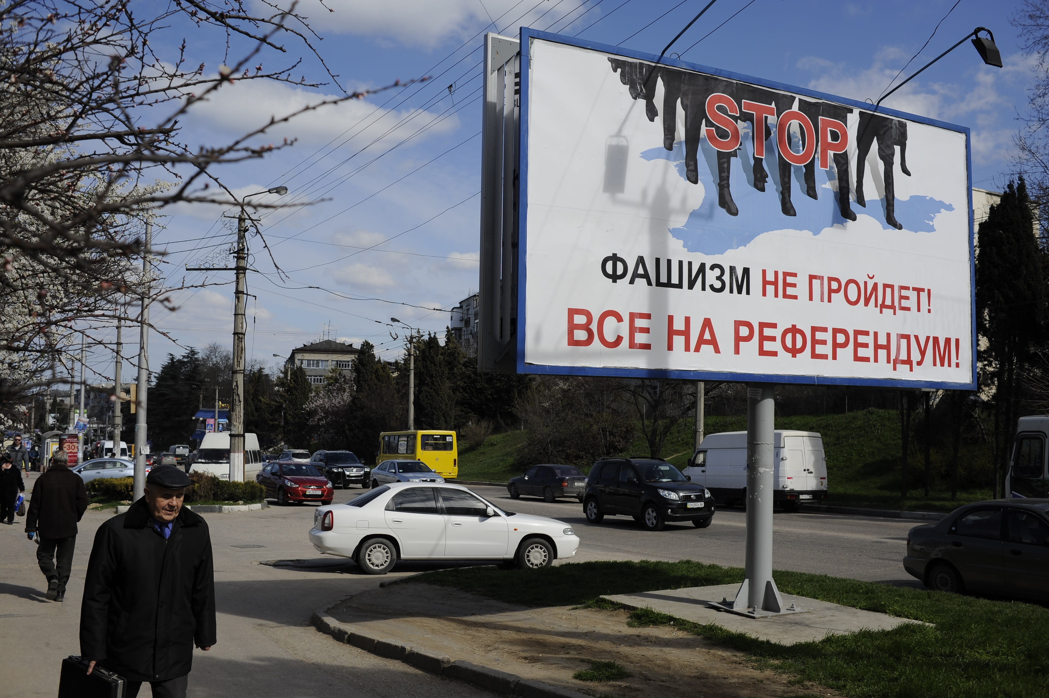 """People walk by a poster reading """"Fascism won't succeed. Everybody to the referendum!"""" in Sevastopol, Thursday, March 13, 2014. Crimea plans to hold a referendum on upcoming Sunday that will ask residents if they want the territory to become part of Russia. Ukraine's government and Western nations have denounced the referendum as illegitimate and warned Russia against trying to annex Crimea. (AP Photo/Andrew Lubimov)"""