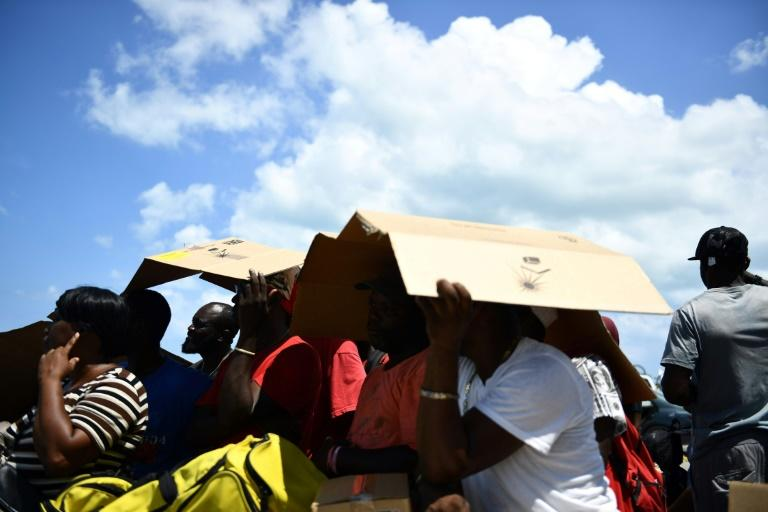 People seek shelter from the sun as they await evacuation at a dock in Marsh Harbour, Bahamas, on September 7, 2019, in the aftermath of Hurricane Dorian (AFP Photo/Brendan Smialowski)