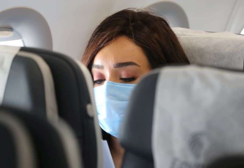 FILE PHOTO: A traveller wears a protective face mask on a plane following an outbreak of the coronavirus disease (COVID-19) in Cairo