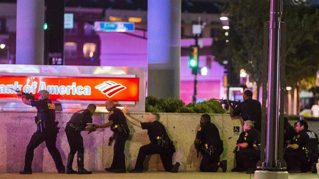 Dallas police officers take cover Thursday night after snipers ambushed cops during a demonstration organized to protest this week's police-involved shootings in Minnesota and Louisiana. (AP)