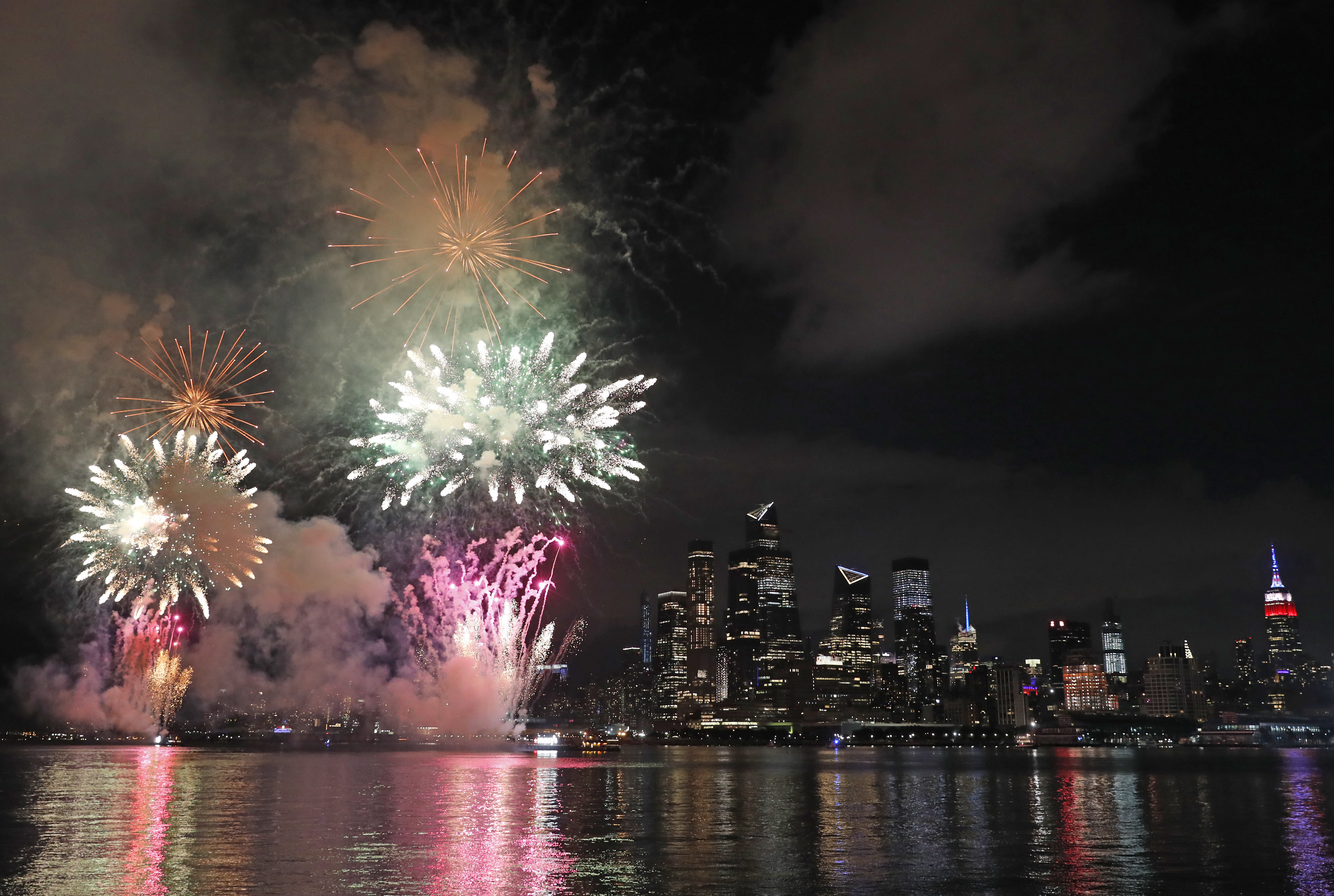 A surprise display of fireworks sponsored by Macy's explode over the Hudson Yards area of Manhattan as seen from a pier in Hoboken, N.J., late Tuesday, June 30, 2020. The fireworks were not announced until an hour or so before to avoid attracting large crowds during the coronavirus pandemic. (AP Photo/Kathy Willens)