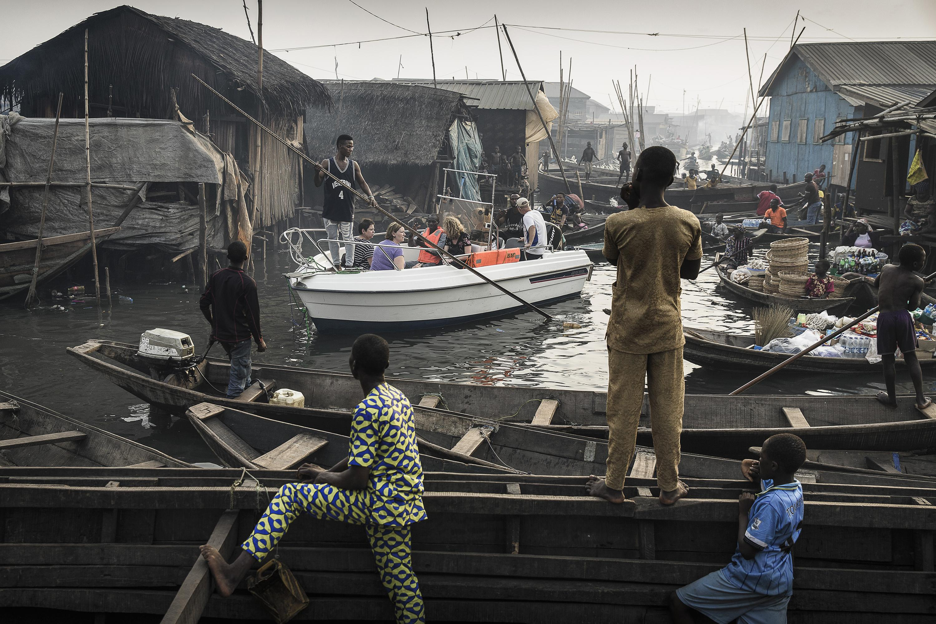 <p>Lagos waterfronts under threat: A boat with expats from Lagos Marina is steered through the canals of Makoko community — an ancient fishing village that has grown into an enormous informal settlement — on the shores of Lagos Lagoon, Lagos, Nigeria, Feb. 24, 2017.<br>Makoko has a population of around 150,000 people, many of whose families have been there for generations. But Lagos is growing rapidly, and ground to build on is in high demand. Prime real estate along the lagoon waterfront is scarce, and there are moves to demolish communities such as Makoko and build apartment blocks: accommodation for the wealthy. Because the government considers the communities to be informal settlements, people may be evicted without provision of more housing. Displacement from the waterfront also deprives them of their livelihoods. The government denies that the settlements have been inhabited for generations and has given various reasons for evictions, including saying that the communities are hideouts for criminals. Court rulings against the government in 2017 declared the evictions unconstitutional and that residents should be compensated and rehoused, but the issue remains unresolved. (Photo: Jesco Denzel) </p>