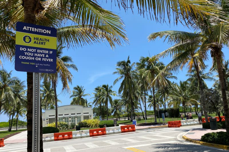 A sign warning about the spread of coronavirus disease is seen in Miami Beach