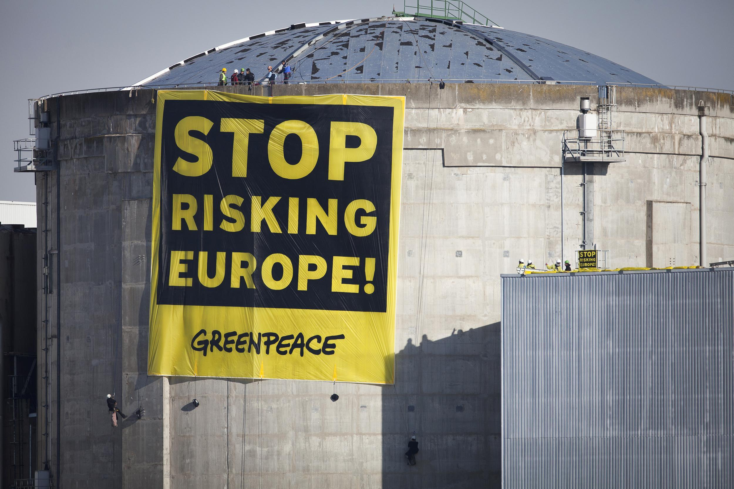 "In this photo provided by environmental group Greenpeace, activisits hang a banner reading ""Stop Risking Europe"" at the Fessenheim nuclear power plant, eastern France, Tuesday, March 18, 2014. More than 60 Greenpeace activists have occupied a nuclear plant in eastern France to protest the nation's reliance on atomic power. In a statement Greenpeace France said the activists had come from 14 countries across Europe ""to denounce the risk to Europe from France's nuclear power,"" and to promote a transition to other energy sources. (AP Photo/Daniel Mueller, Greenpeace) NO ARCHIVE"