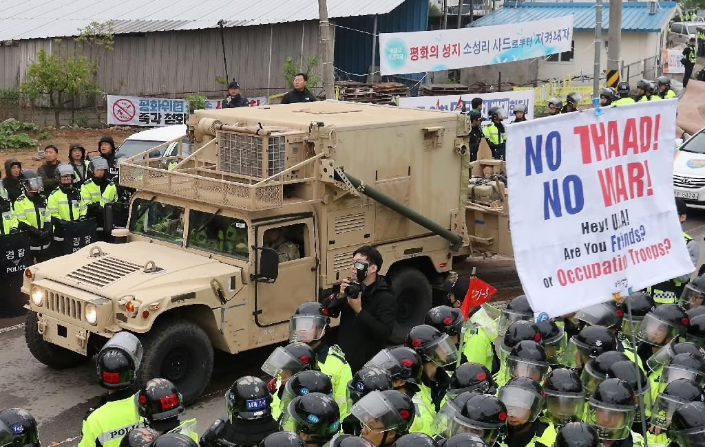 Protesters and police stand by as trailers carrying US THAAD missile defence equipment enter a deployment site in Seongju, on April 26, 2017 (AFP Photo/YONHAP)