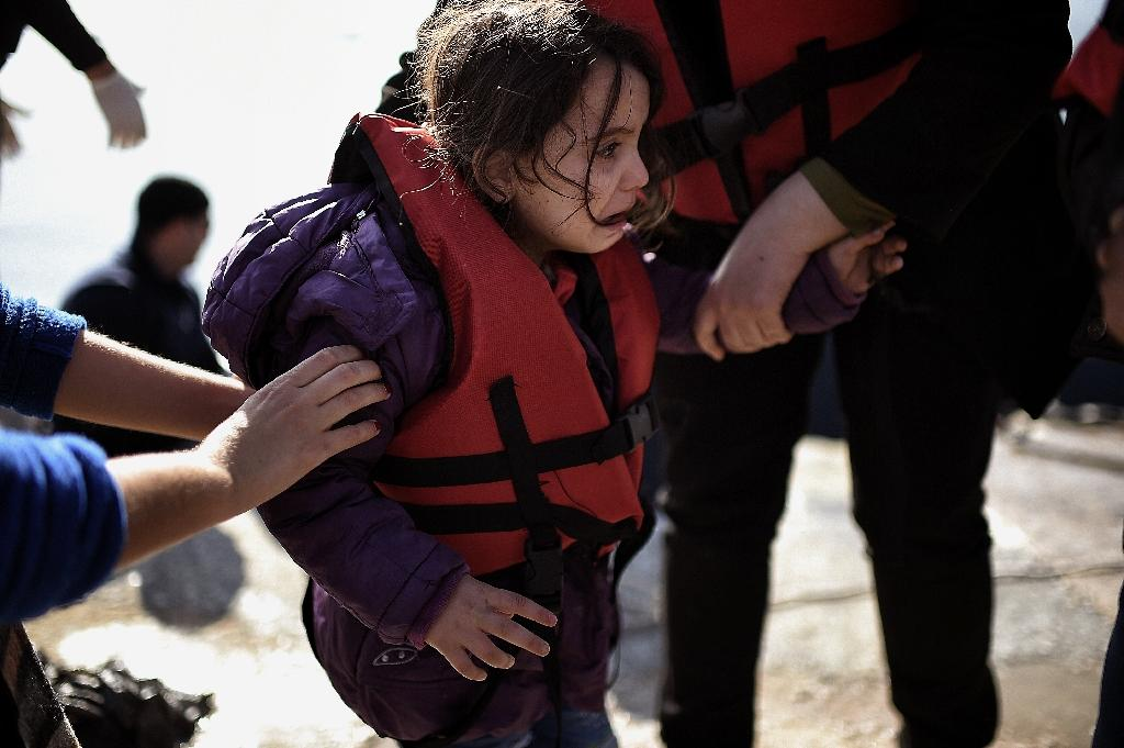 Greek authorities help a migrant child disembark on the Greek island of Lesbos after crossing the Aegean sea from Turkey, on February 18, 2016 (AFP Photo/Aris Messinis )