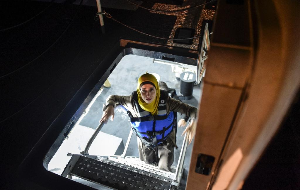 A Syrian migrant woman climbs stairs aboard the Turkish Coast Guard ship Umut, after a group of migrants was rescued from an inflatable dinghy attempting to reach the Greek Island Chios on December 9, 2015 (AFP Photo/Bulent Kilic)