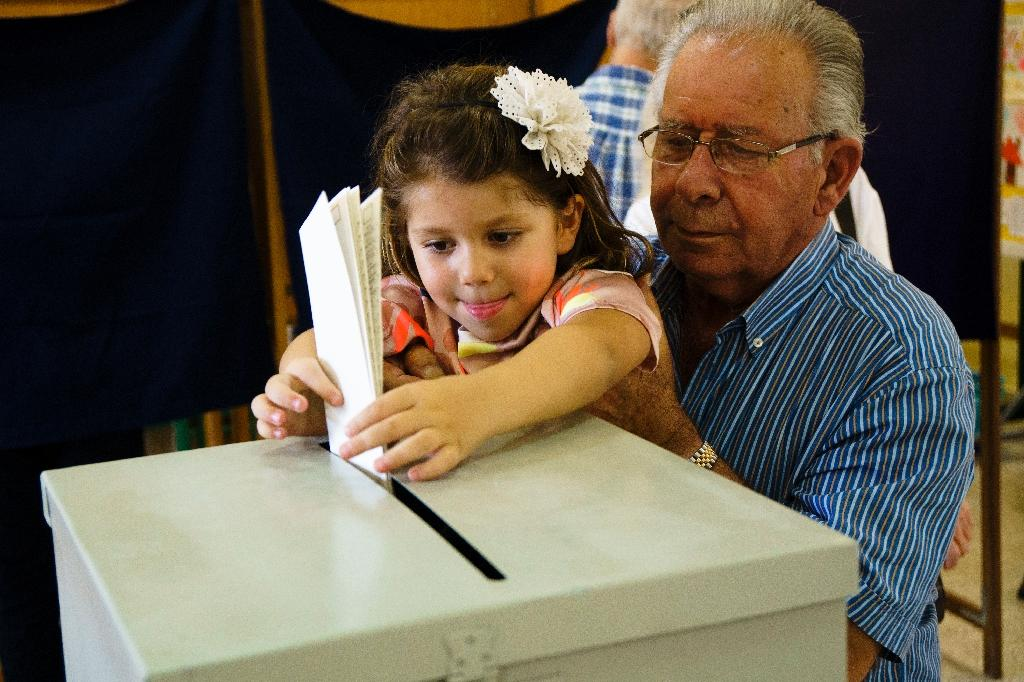 A Cypriot girl casts the ballot of her relative for the parliamentary elections at a polling station in the capital Nicosia on May 22, 2016 (AFP Photo/Iakovos Hatzistavrou)