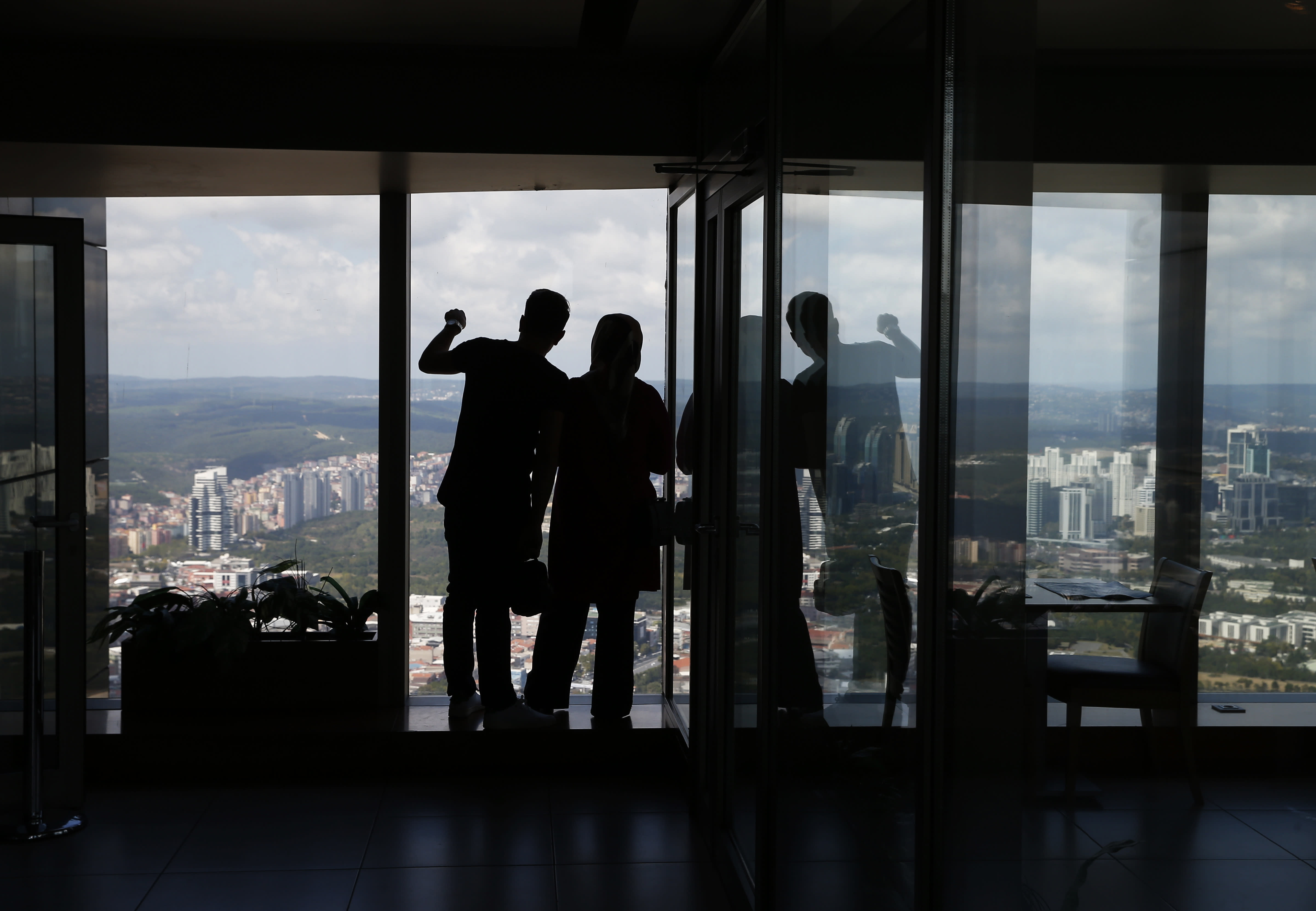 Tourists enjoy the views from a high-rise building's observation deck in Istanbul, Thursday, Aug. 16, 2018. Beset by a weak currency and tension with the United States, Turkey is reaching out to Europe in an attempt to shore up relations with major trading partners despite years of testy rhetoric and a stalled bid for EU membership. The overtures by Turkish President Recep Tayyip Erdogan, who has harshly criticized Germany and other European nations in the past, are part of a diplomatic campaign to capitalize on international unease over U.S. President Donald Trump and American tariff disputes. (AP Photo/Lefteris Pitarakis)