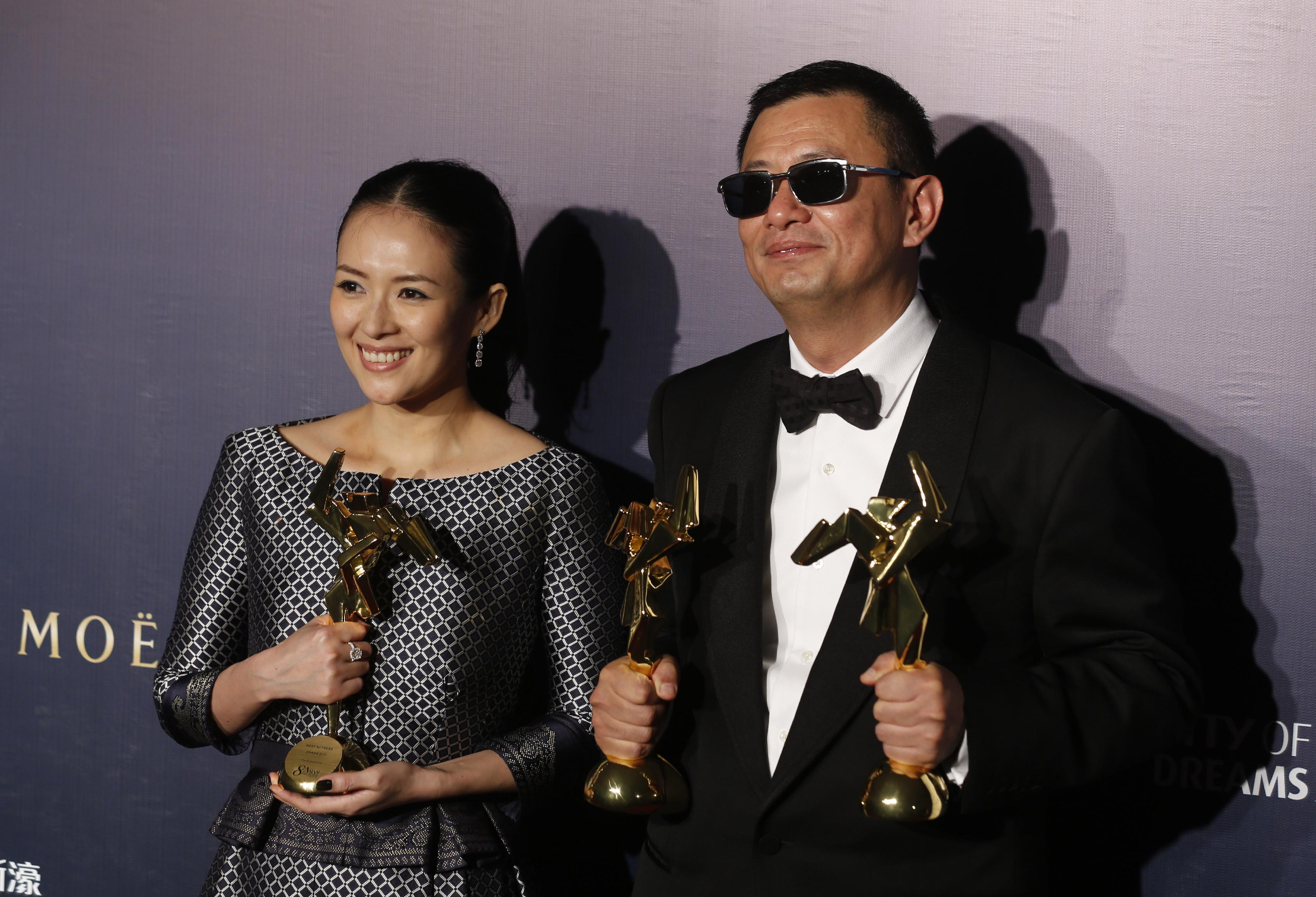 """Hong Kong director Wong Kar-wai, right, and Chinese actress Zhang Ziyi pose after winning the Best Director, the Best Movie and the Best Actress for their movie """"The Grandmaster,"""" of the Asian Film Awards in Macau Thursday, March 27, 2014. (AP Photo/Kin Cheung)"""