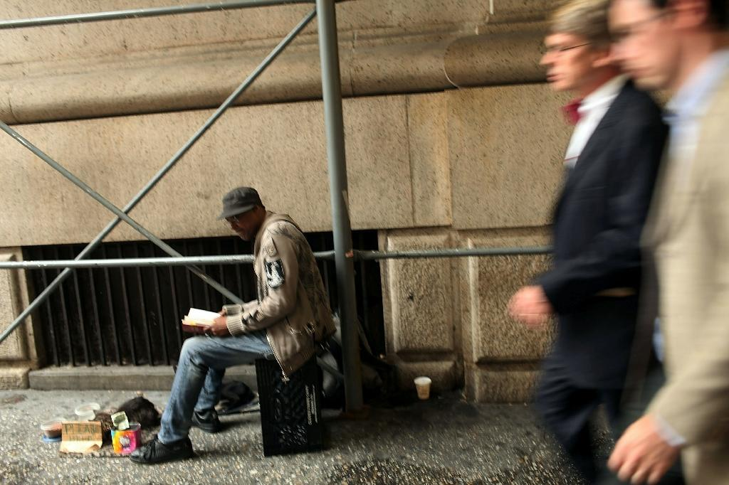 Businessmen walk by a homeless man on the street on September 28, 2010 in New York