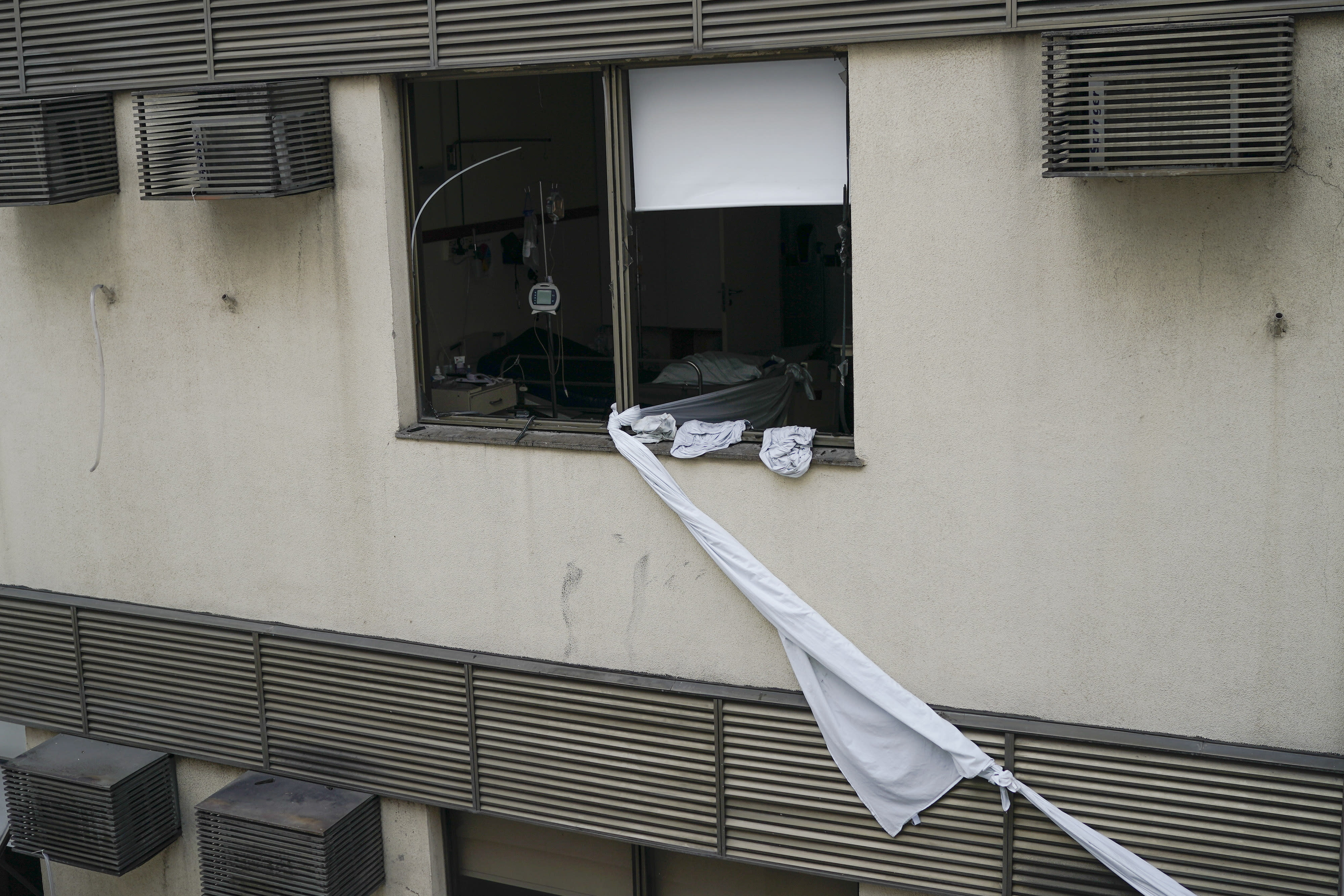 A rope made of bedsheets that was used to escape from the upper floor of the Badim Hospital, is seen tied to a window, where a fire left at least 11 people dead, in Rio de Janeiro, Brazil, Friday, Sept. 13, 2019. The fire raced through the hospital forcing staff to wheel patients into the streets on beds or in wheelchairs. (AP Photo/Leo Correa)