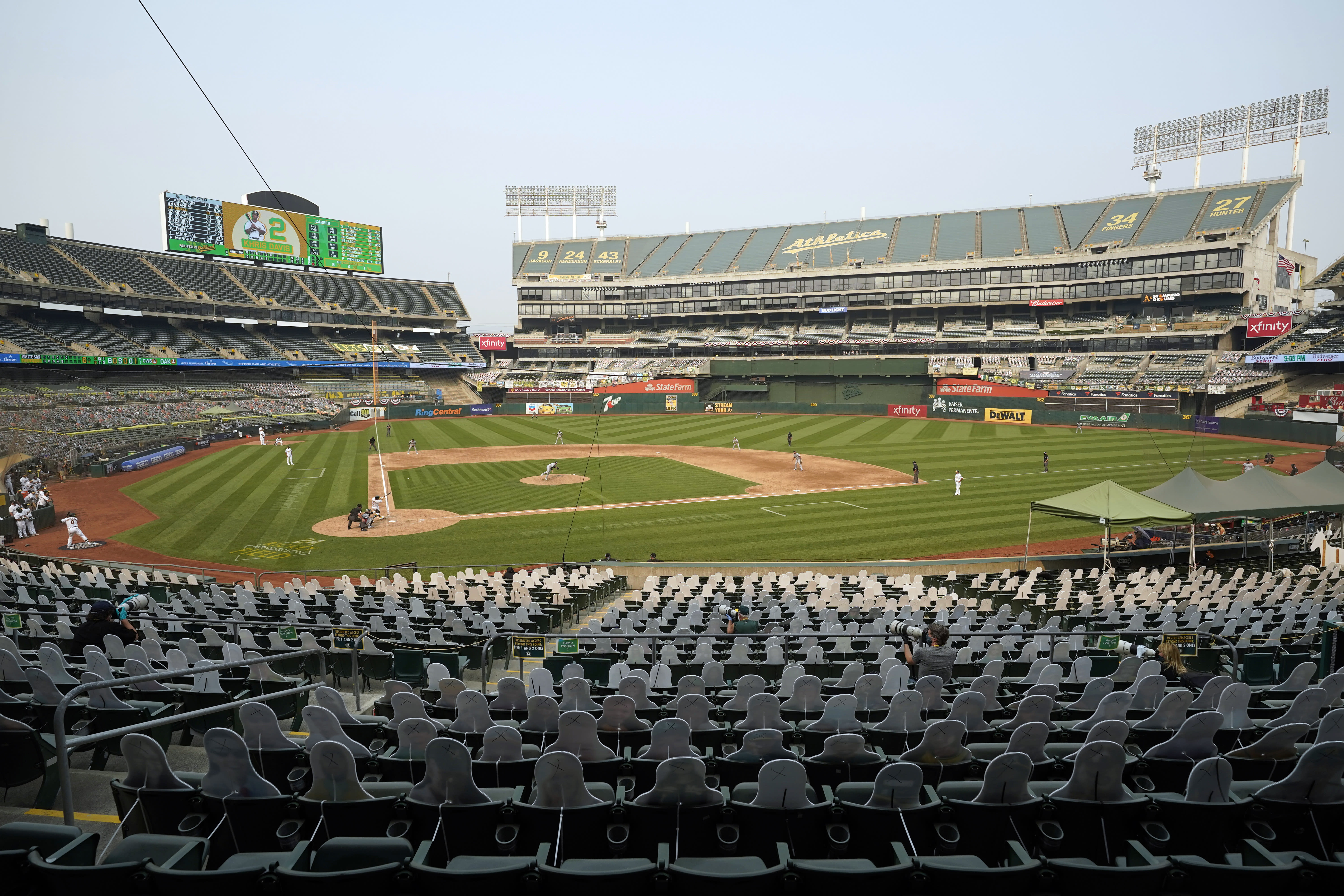 Oakland Athletics' Khris Davis hits a single off Chicago White Sox pitcher Evan Marshall in front of cutouts seated at Oakland Coliseum during the sixth inning of Game 3 of an American League wild-card baseball series Thursday, Oct. 1, 2020, in Oakland, Calif. (AP Photo/Eric Risberg)