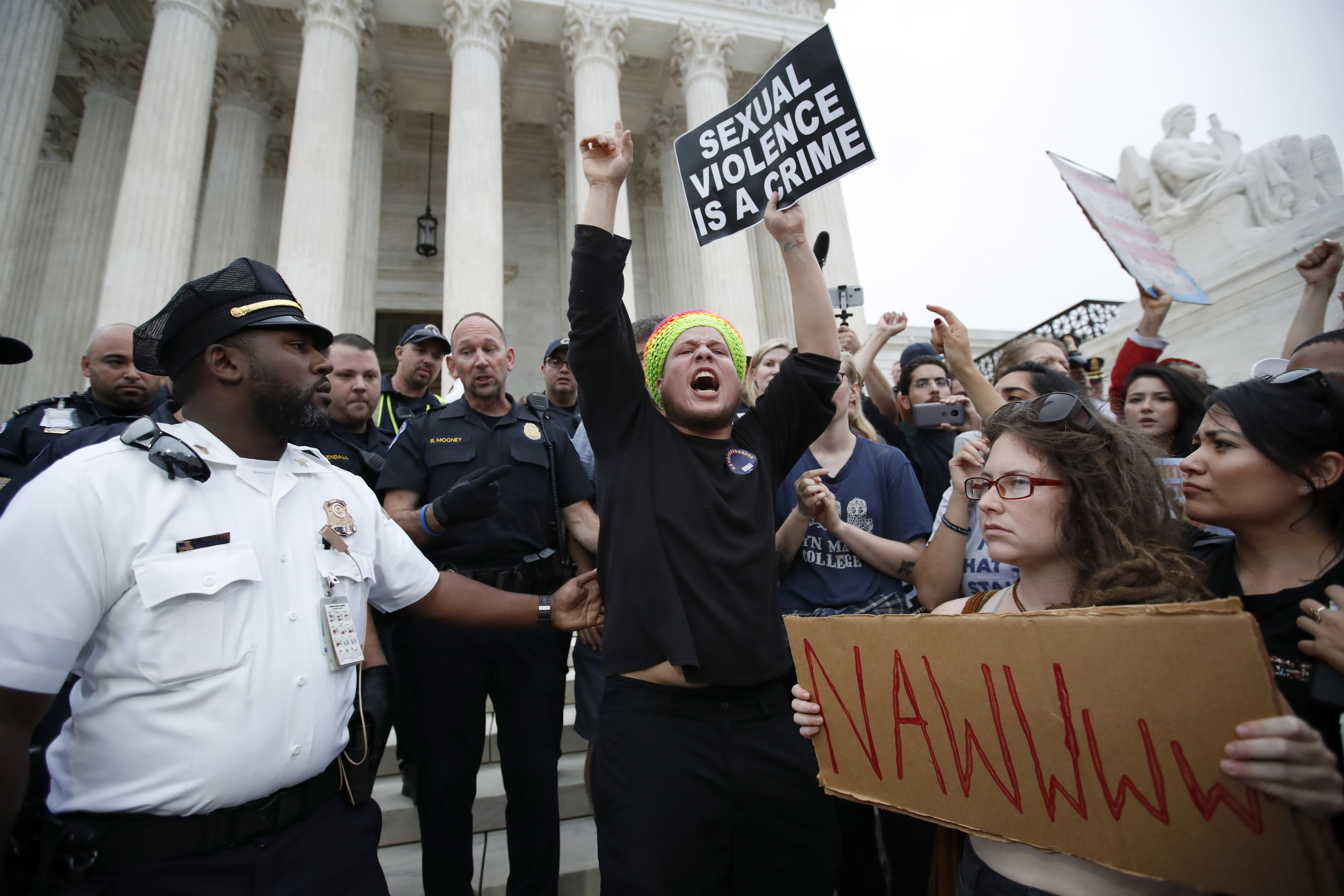 <p>Police move activists as they protest on the steps of the Supreme Court after the confirmation vote of Supreme Court nominee Brett Kavanaugh, on Capitol Hill, Saturday, Oct. 6, 2018 in Washington. (Photo: Alex Brandon/AP) </p>