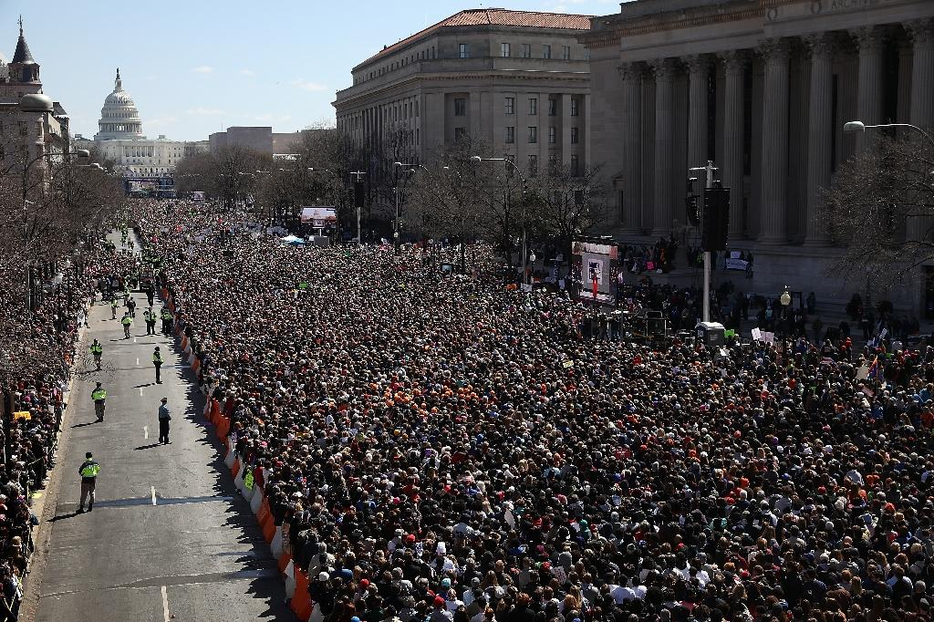 Gun reform advocates line Pennsylvania Avenue while attending the March for Our Lives rally March 24, 2018 in Washington, DC (AFP Photo/WIN MCNAMEE)