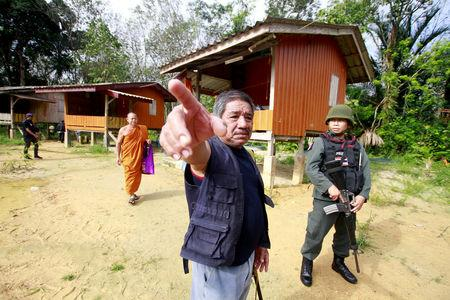 Military police officers and a buddhist monk are seen at a temple where unknown gunmen shot dead two Buddhist monks and injured two others on Friday in Su-ngai Padi district in the southern province of Narathiwat, Thailand, January 19, 2019. REUTERS/Surapan Boonthanom