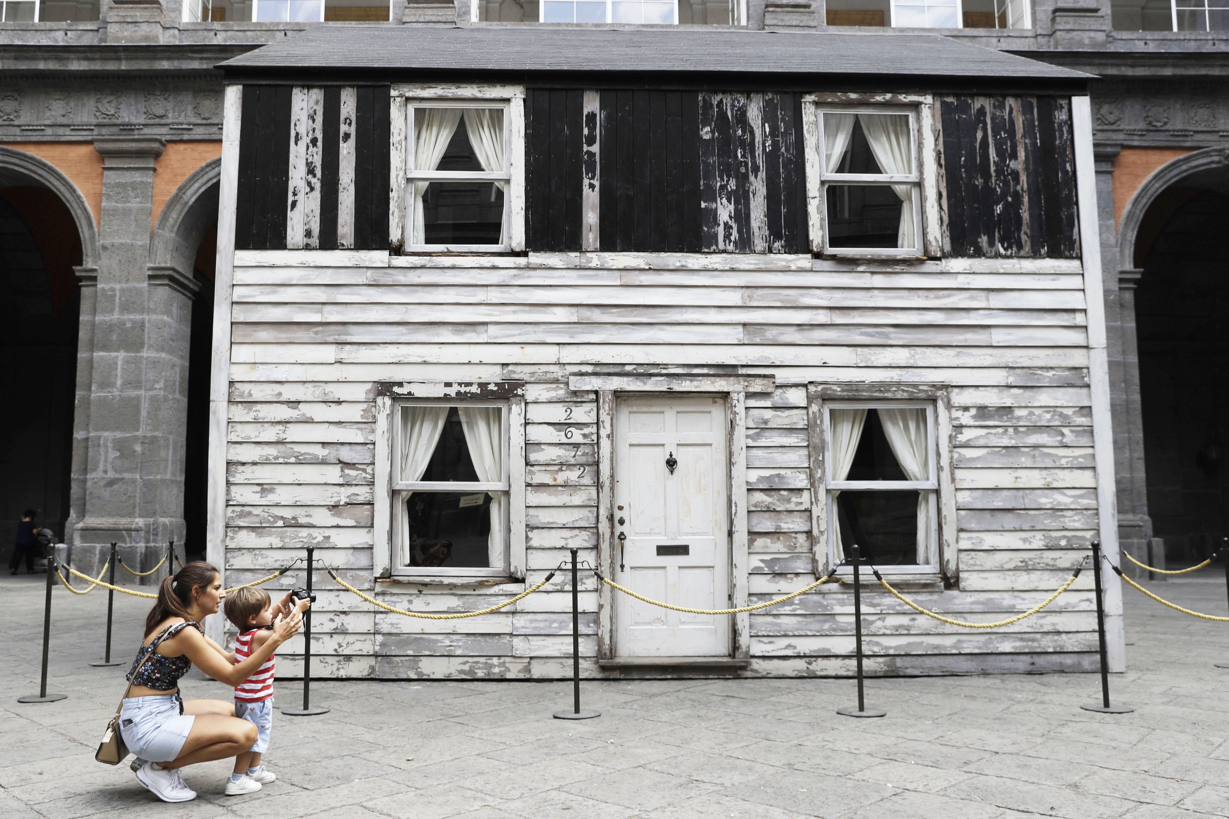 Alice Ridolfi, from Verona, helps her two years old son Leone take pictures of the house of U.S. civil rights campaigner Rosa Parks, rebuilt by artist Ryan Mendoza for public display, in Naples, Italy, Tuesday, Sept. 15, 2020. The rundown, paint-chipped Detroit house where Parks took refuge after her famous bus boycott is going on display in a setting that couldn't be more incongruous: the imposing central courtyard of the 18th century Royal Palace. (AP Photo/Gregorio Borgia)