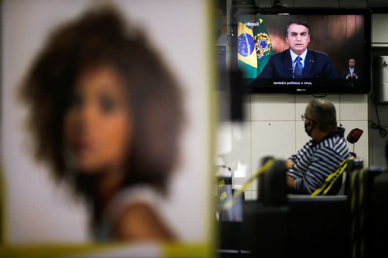 Brazil's President Jair Bolsonaro is seen on a tv screen in a beauty salon as he speaks in a video recorded speech for the 75th session of the United Nations General Assembly, in Brasilia