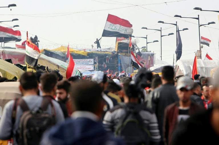This photo taken on December 10, 2019 shows Iraqi protesters on Baghdad's Al-Sinek bridge, where a demonstrator was killed by a tear gas canister on Friday