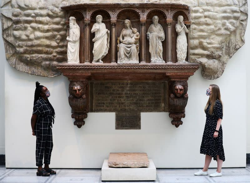 Museum gallery assistants pose for members of the media in front of the 'Monument of Marchese Spinetta Malaspina' during preparations to reopen the Victoria & Albert (V&A) Museum, in London