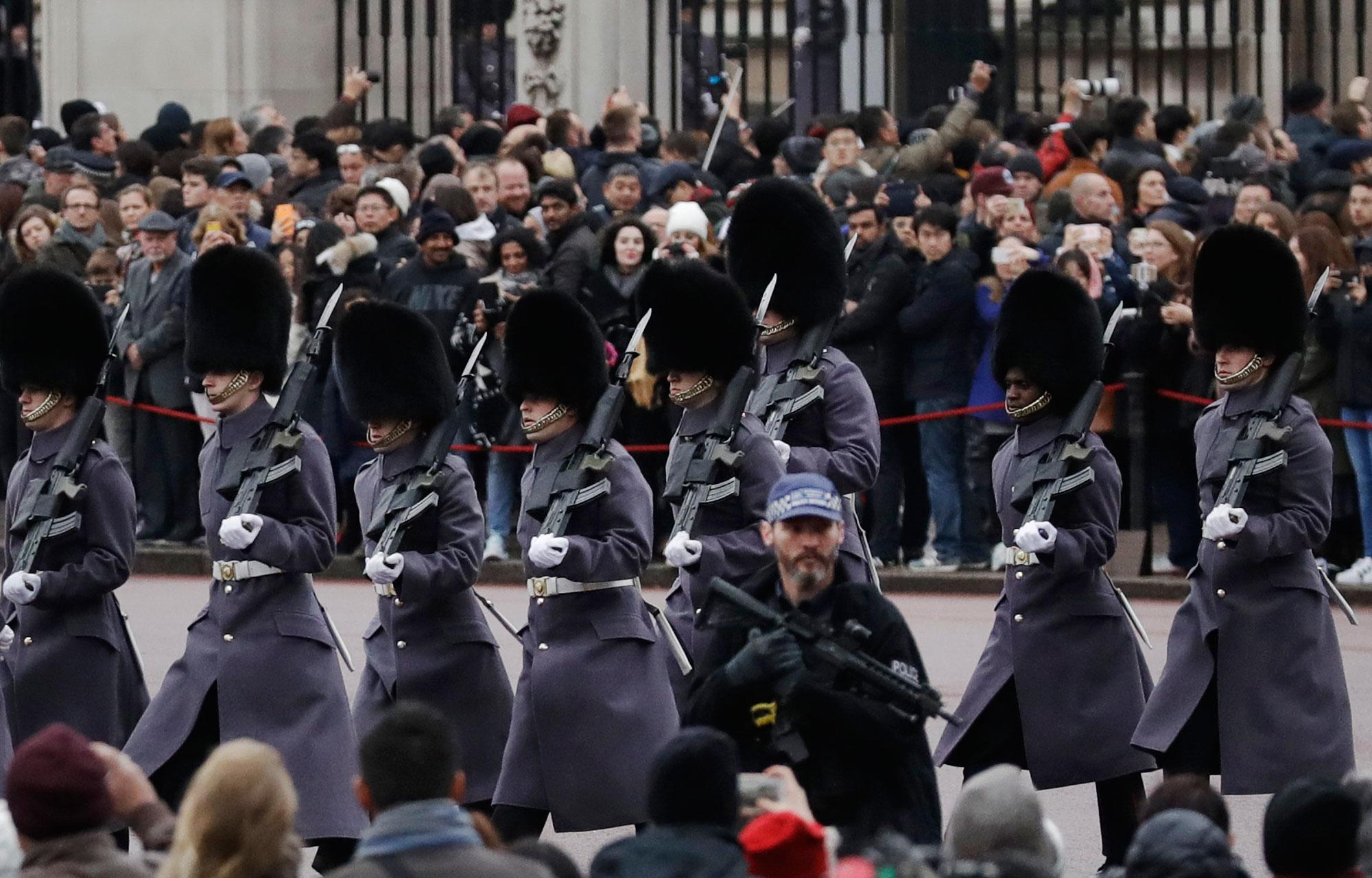 <p>An armed police officer stands guard in the foreground as members of the British military march past, during the Changing the Guard ceremony outside Buckingham Palace in London, Wednesday, Dec. 21, 2016. London police on Wednesday instituted road closures in the area surrounding Buckingham Palace for nearly two hours while the popular Changing the Guard military ceremony was taking place — a security measure rushed into place because of the deadly Christmas market truck attack in Berlin. (Photo: Matt Dunham/AP) </p>
