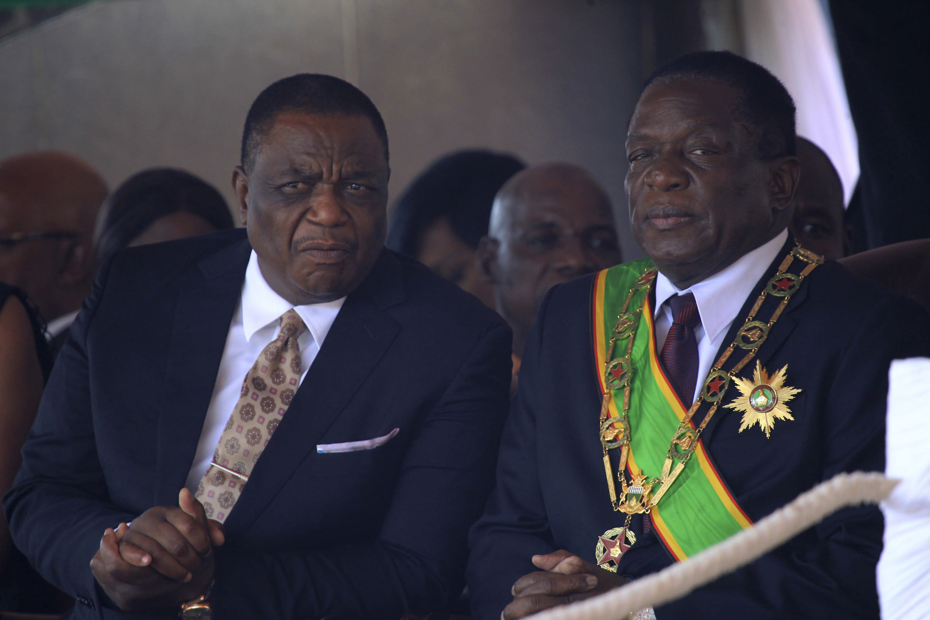 FILE - In this Monday, Aug. 13, 2018, file photo, Zimbabwe's President Emmerson Mnangagwa, right, sits with his Deputy Constantino Chiwenga, left, during a Heroes' Day event in Harare, Zimbabwe. The coronavirus pandemic could narrow one gaping inequality in Africa, where some heads of state and other elite jet off to Europe or Asia for health care unavailable in their nations but as global travel restrictions tighten, they might have to take their chances at home. (AP Photo/Tsvangirayi Mukwazhi, File)