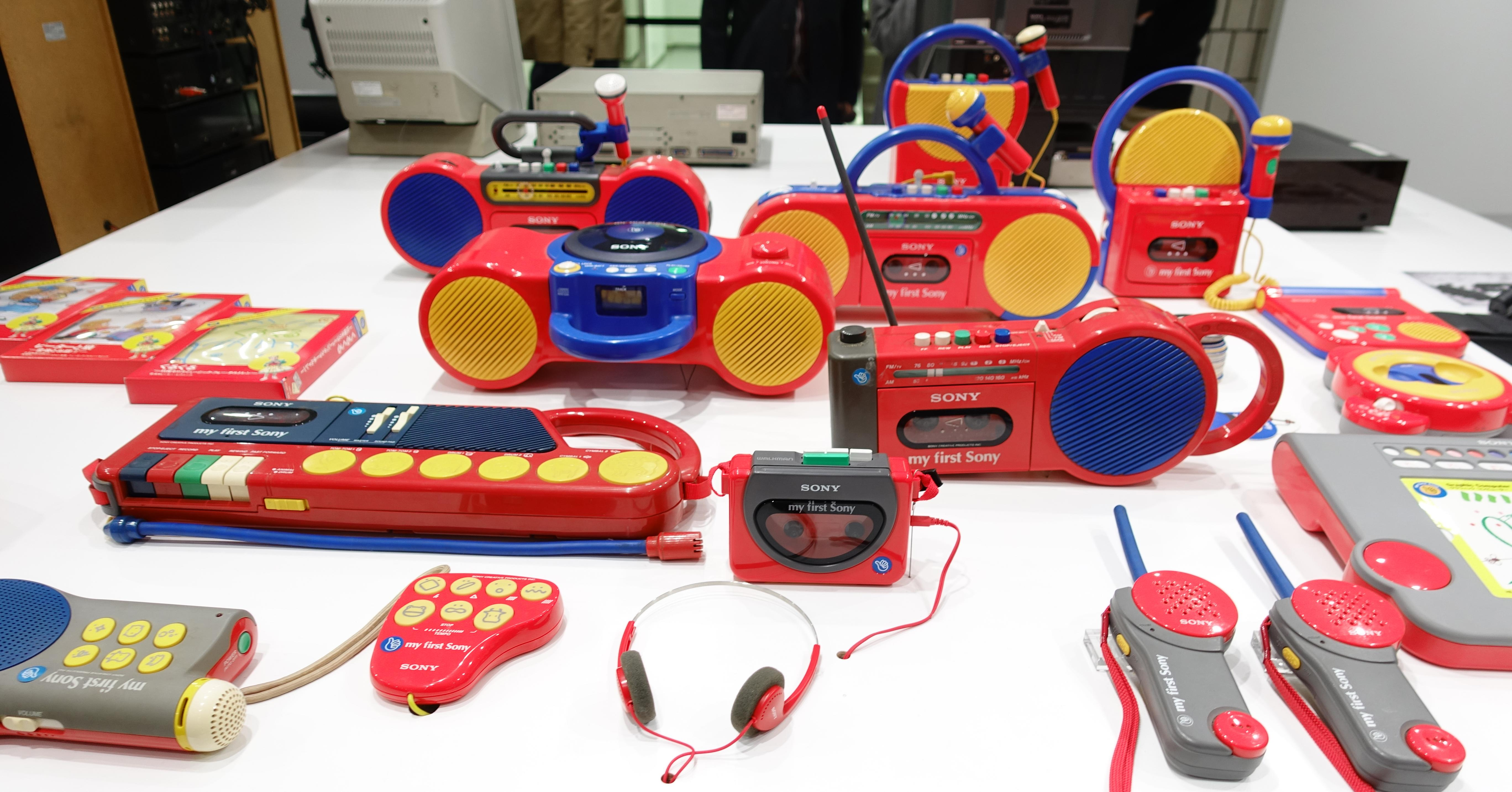 Array of My First Sony products on a table, including several tape players, walkie-talkies and a pair of headphones.