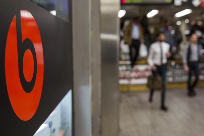 Commuters walk past a Beats brand display in the subway system of New York, May 29, 2014. Apple Inc will buy Beats for about $3 billion and bring recording mogul Jimmy Iovine into its ranks, hoping to win points with the music industry and help it catch up in fast-growing music streaming. As expected, Beats co-founders Iovine and rapper Dr. Dre will join Apple as part of the acquisition of the music streaming and audio equipment company.    REUTERS/Lucas Jackson (UNITED STATES - Tags: BUSINESS)