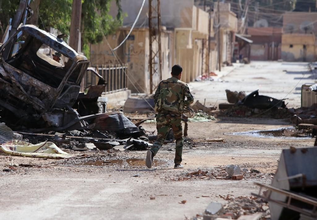 A Syrian regime soldier walks near a destroyed vehicle in the northeastern city of Hasakeh, on July 13, 2015 (AFP Photo/Youssef Karwashan)
