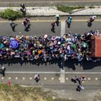 Migrant caravan pauses to remember dead as Donald Trump blames Democrats for 'assault on our country'