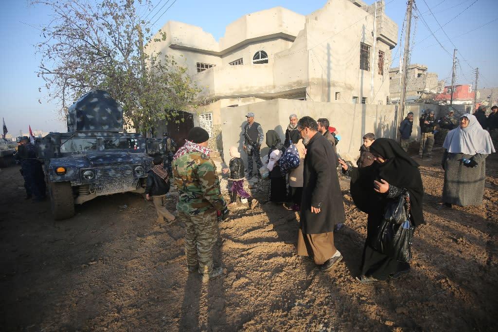 Members of the Iraqi forces evacuate civilians fleeing Mosul's eastern Al-Intisar neighbourhood on December 30, 2016, during an ongoing military operation against Islamic State (IS) group jihadists (AFP Photo/AHMAD AL-RUBAYE)