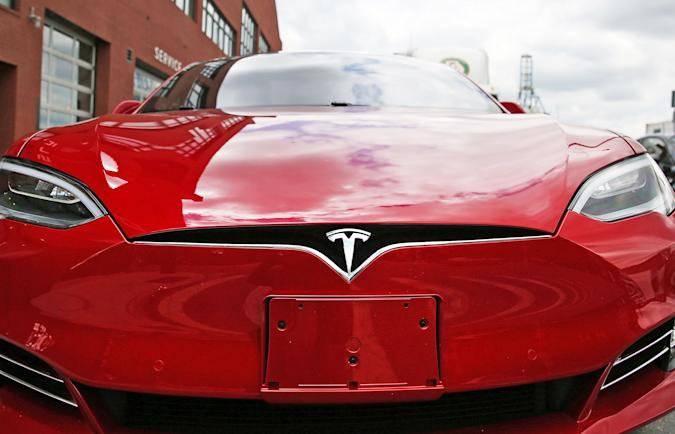 A closeup of a red Tesla's front grill / bumper.
