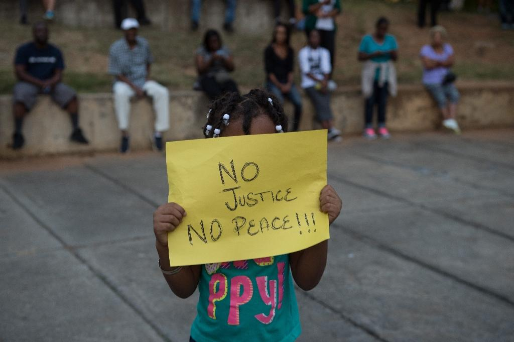 A little girl holds up a sign during a demonstration against police brutality in Charlotte, North Carolina, on September 21, 2016 (AFP Photo/Nicholas Kamm)