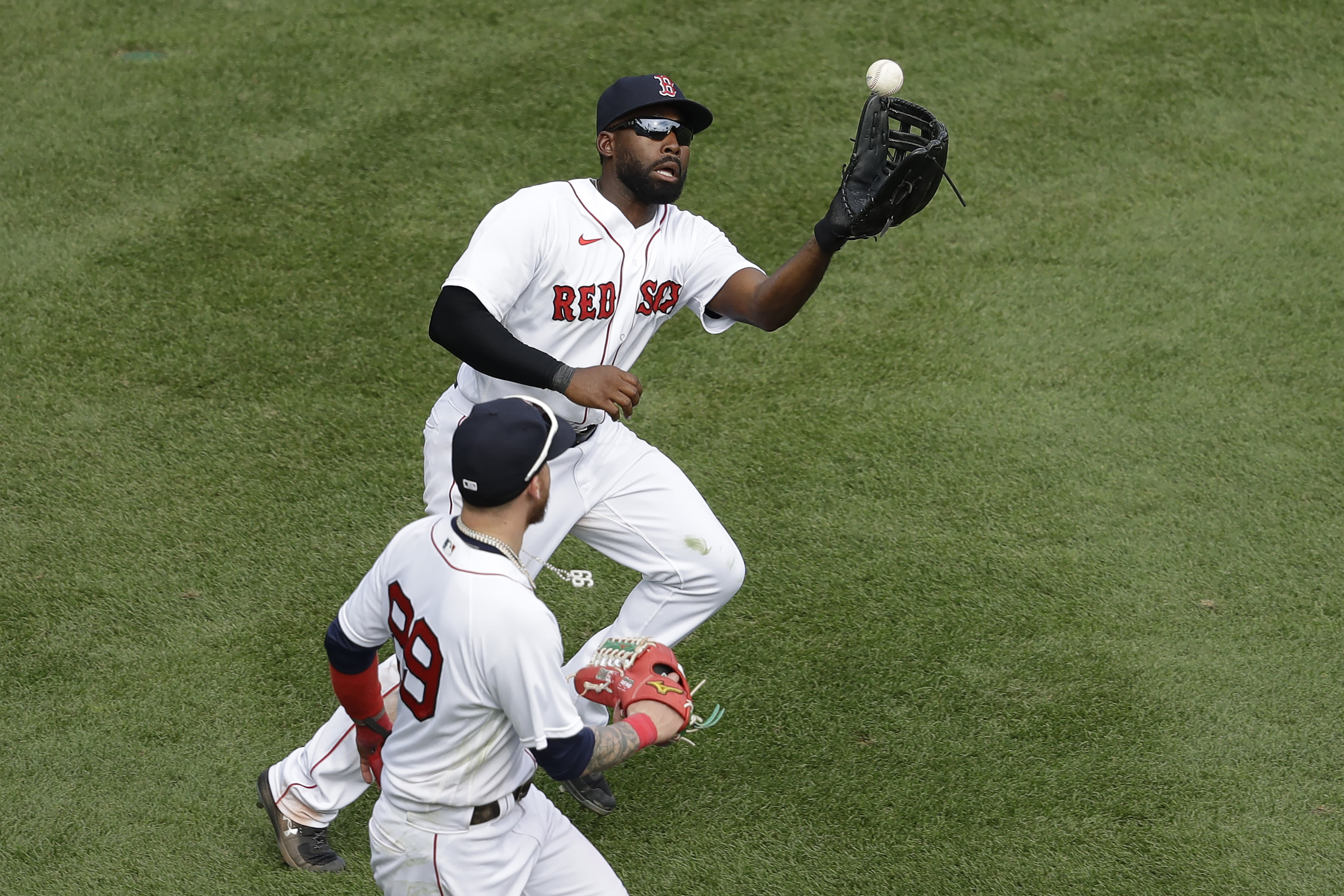 Boston Red Sox's Jackie Bradley Jr., top, gets his glove on an RBI-single by Baltimore Orioles' Chris Davis after the ball bounced off the Green Monster wall as Alex Verdugo, bottom, runs beside him during the ninth inning of a baseball game, Sunday, July 26, 2020, in Boston. (AP Photo/Steven Senne)