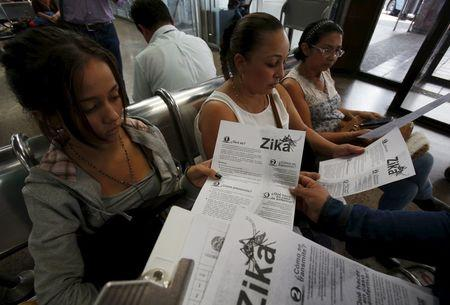 Colombian women listen as a health worker distributes information how to prevent the spread of the Zika virus, at the transport terminal in Bogota, Colombia