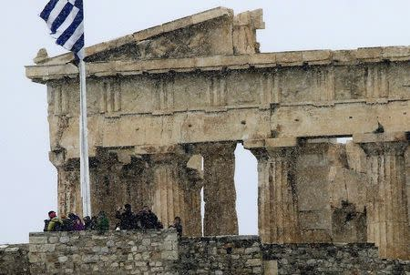 Tourists take photos atop the Athens Acropolis during a snowstorm