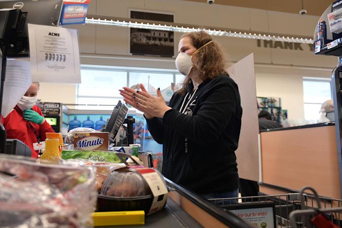 CLARK, NEW JERSEY - APRIL 27: Clark resident Jen Valencia sanitizes her hands at checkout as she supplements her income working for Instacart at Acme Market on April 27, 2020 in Clark, New Jersey. Instacart has experienced a massive surge in customer demand and employment recently due to lockdowns and other restrictions caused by COVID-19. (Photo by Michael Loccisano/Getty Images)