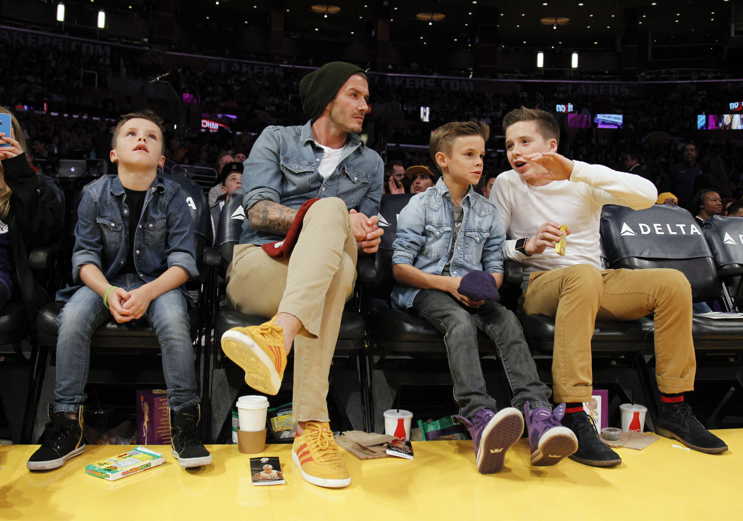 British soccer player David Beckham (2nd L) sits courtside with his sons Cruz (L), Romeo (2nd R) and Brooklyn (R) during the NBA basketball game between the Los Angeles Lakers and Phoenix Suns in Los Angeles November 16, 2012. REUTERS/Danny Moloshok (UNITED STATES - Tags: SPORT BASKETBALL ENTERTAINMENT SOCCER)